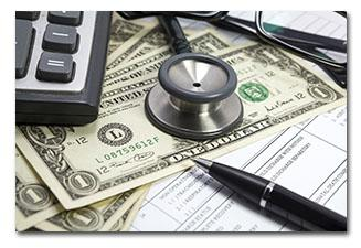 Money  laying on medical forms under the corner of a calculator with a stethoscope laying on top