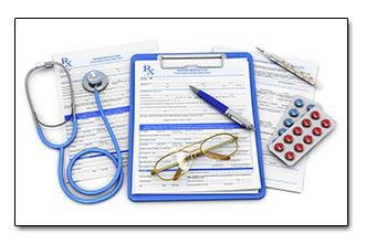 Medical forms on a clipboard with a stethoscope, pens, glasses, and pills in a blister pack