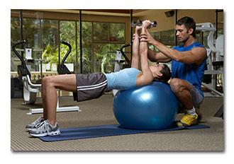 Personal trainer assisting woman on exercise ball holding weights