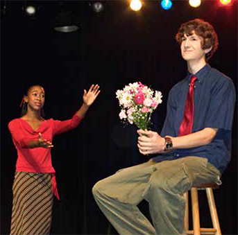 Actor on stool holding flowers with actress addressing actor